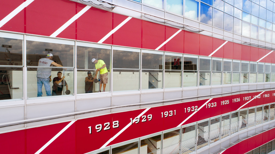 An installation crew from Glass Edge installs new window systems in the club suites of west Memorial Stadium. The windows were designed by Chad Bloomquist, who utilized resources available at Nebraska Innovation Studio to turn his idea into reality.