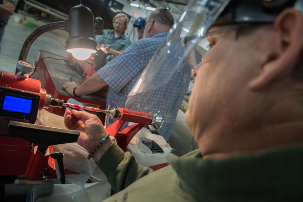 Lee Schon turns a pen tube on a lathe during a Veterans in Recovery meeting at Nebraska Innovation Studio.