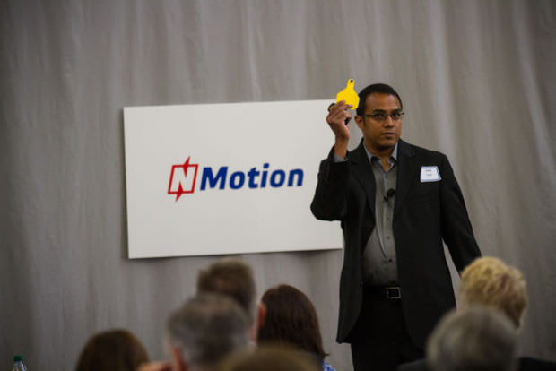 Vishal Singh of QuantifiedAg shows one of the tags he uses to identify and track sick cattle in feedlots at NMotion's day of demonstrations by its 2014 class of startup businesses.