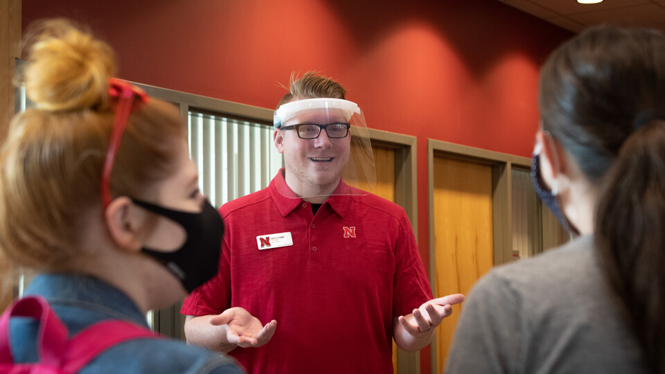 David Strang, an events associate with Academic Services and Enrollment Management, wears a face shield from Nebraska Innovation Campus while visiting with fellow Huskers. The face shields will be distributed to offices and colleges across campus to support students who are deaf or hard of hearing.