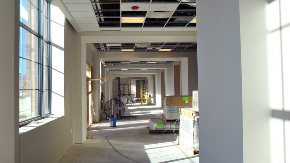 A construction worker sands drywall in a redesigned 4-H Building hallway on Nebraska Innovation Campus.