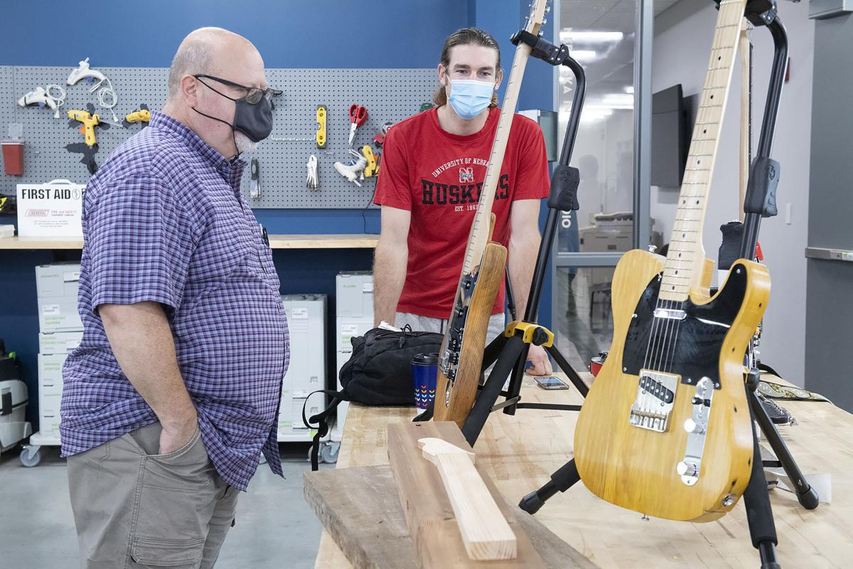 Phil Whitmarsh (left) and Broderick Fielding, who both make guitars, talk about their instruments during an open house at Nebraska Innovation Studio on Thursday. Photo: Gwyneth Roberts, Journal Star