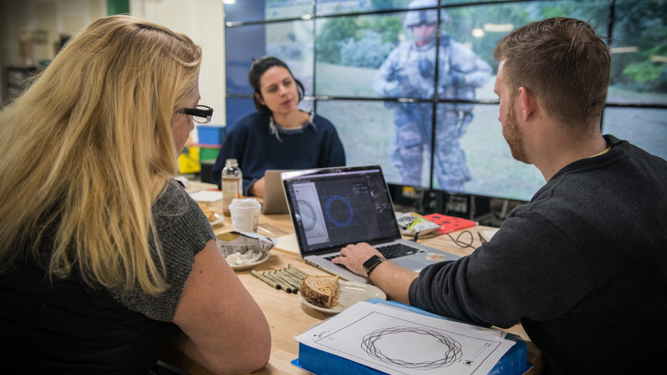 Veteran Melissa Ewing (left), Kendra Clapp Olguin, Has Heart communications director, and Husker alum Jordan Lambrecht work on the artwork representing Ewing's life story. Behind them, on screens at Nebraska Innovation Studio, is a photograph from Ewing's tour in Afghanistan.