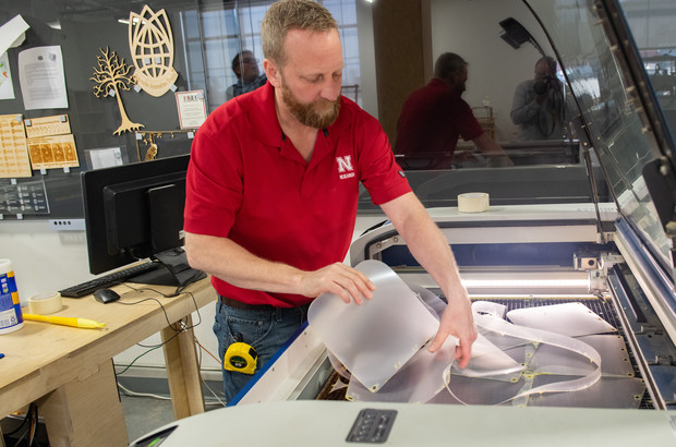 Jerry Reif, shop manager at Nebraska Innovation Studio, works on a laser to cut clear plastic sheeting for face shields. The face shields are being assembled for hospitals in Nebraska in response to COVID-19.