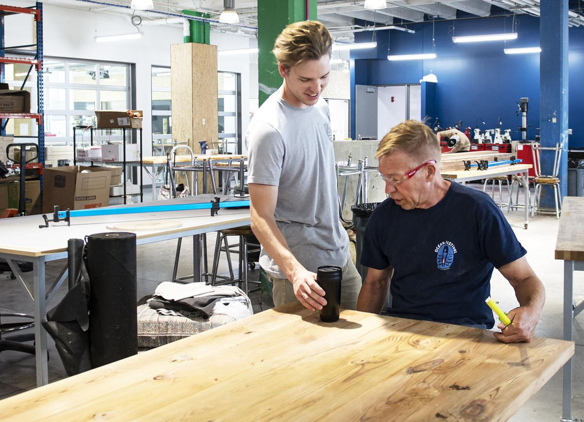 Will Cox (left) places a cup of in front of his dad, Brian, as they test out a table they are building at Nebraska Innovation Studio. The table, built out of reclaimed wood from Habitat for Humanity of Omaha, will be given to a family affected by the flooding this spring.
