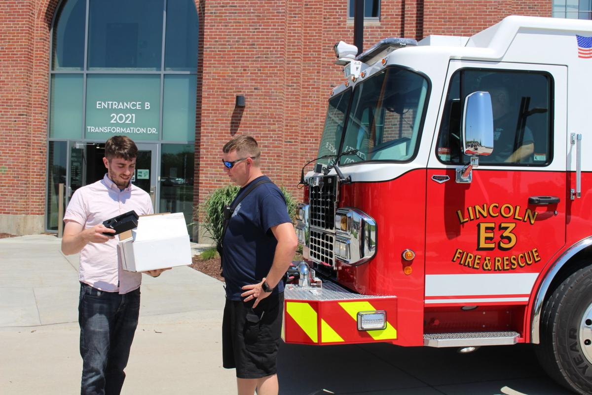 Max Wheeler, instructional designer at Nebraska Innovation Studio, shows a new 3D-printed case for a video laryngoscope to firefighter-paramedic Brennan Oliverius at Nebraska Innovation Campus.