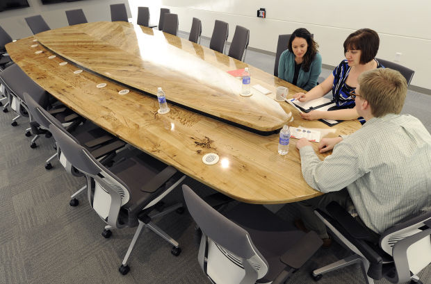 Cheryl Horst (from left), Rose Robotham and Phill Bakken, of NUtech Ventures work Monday at the boardroom table in the Innovation Commons building on Innovation campus. The table was built using green ash from trees cut down at the former State Fair Park.