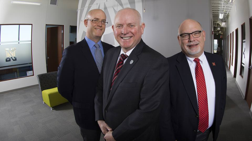 Ryan Anderson, Dan Duncan and Bradley Roth pose in the lobby of Nebraska Innovation Campus' offices. The trio leads a campus network that helps UNL researchers commercialize their work.