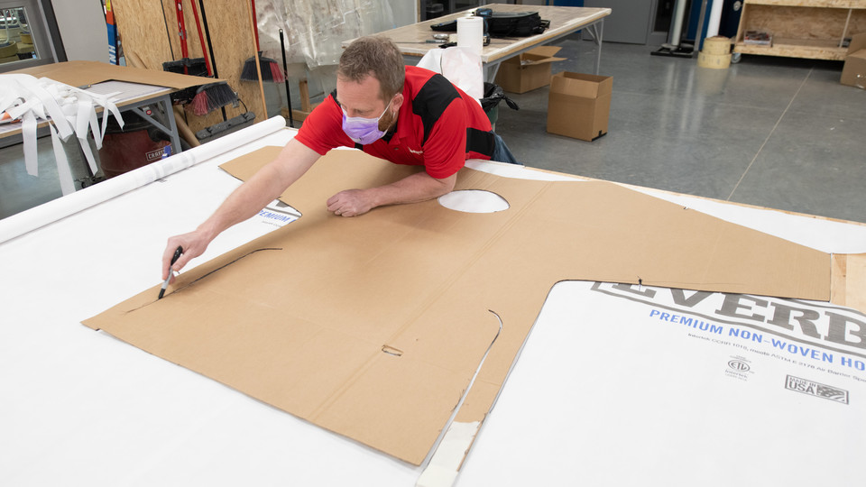 Jerry Reif, studio manager at Nebraska Innovation Studio, cuts out a gown form from Tyvec material.
