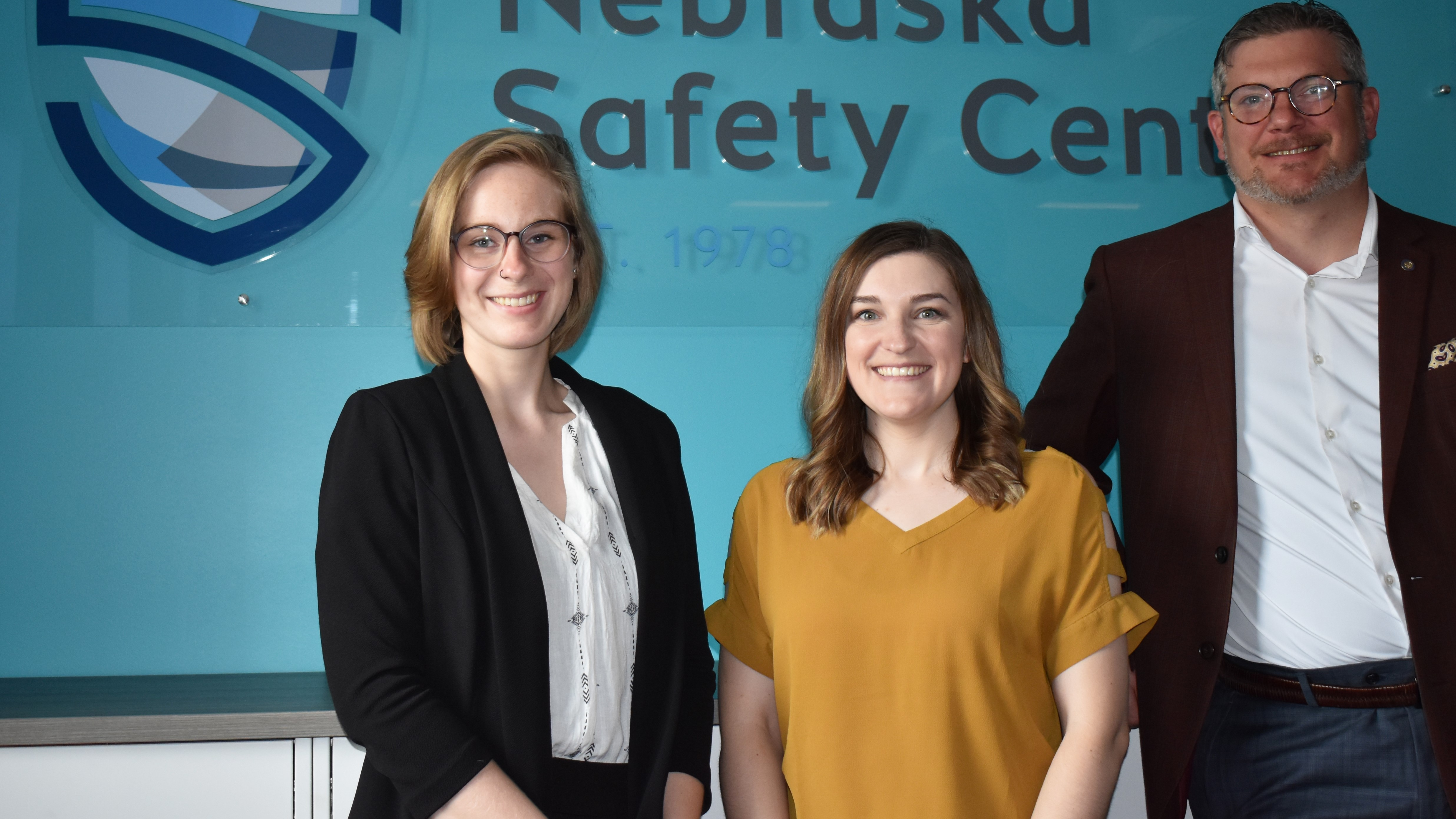 Nebraska Safety Center staff standing in front of a teal wall and logo sign